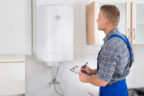 Man With Clipboard While Looking At Electric Boiler Stock photo © AndreyPopov