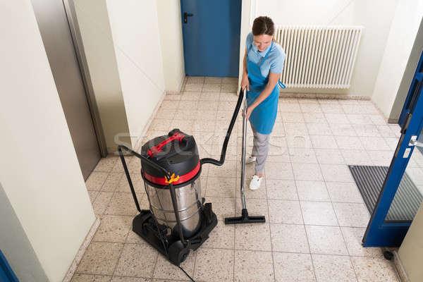 Kobiet woźny czyszczenia piętrze młodych odkurzacz Zdjęcia stock © AndreyPopov
