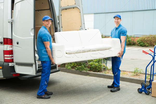 Workers Putting Furniture And Boxes In Truck Stock photo © AndreyPopov