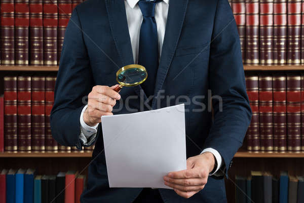 Lawyer Examining Legal Documents With Magnifying Glass Stock photo © AndreyPopov