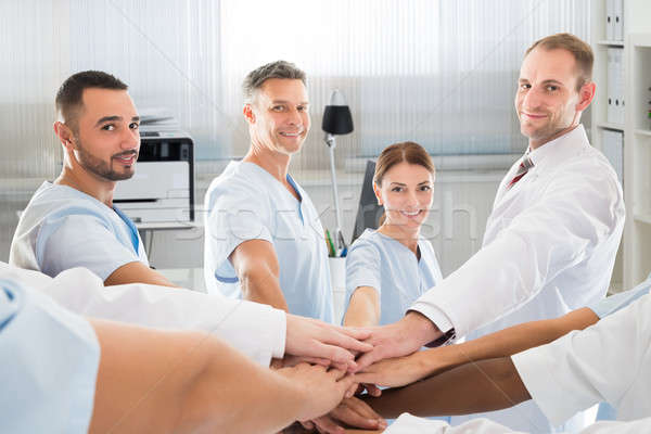 Confident Medical Team Smiling While Joining Hands Stock photo © AndreyPopov