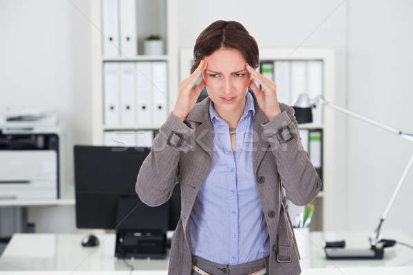 Businesswoman Suffering From Headache In Office Stock photo © AndreyPopov
