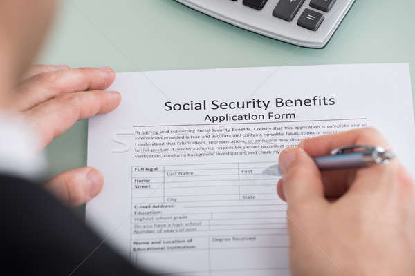 Person Hand Filling Social Security Benefits Form Stock photo © AndreyPopov