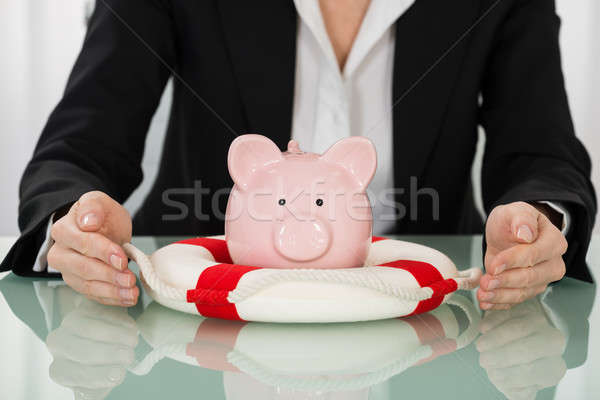 Businesswoman Hand Protecting Piggybank With Lifebelt Stock photo © AndreyPopov
