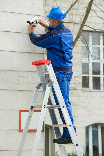 Male Technician Standing On Stepladder Fitting CCTV Camera Stock photo © AndreyPopov