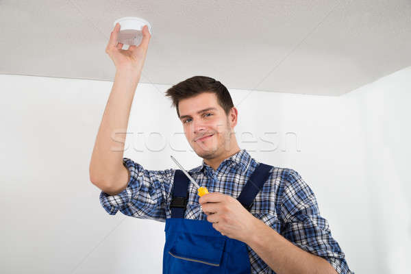Stock photo: Electrician Repairing Fire Sensor