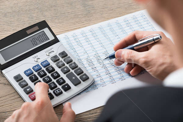 Businessman Analyzing Accounting Document With Calculator Stock photo © AndreyPopov