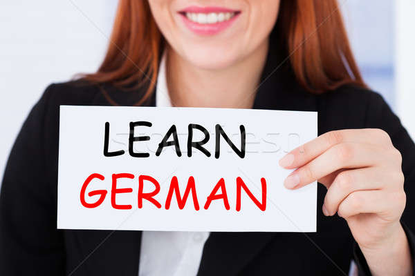 Businesswoman Holding Learn German Card Stock photo © AndreyPopov
