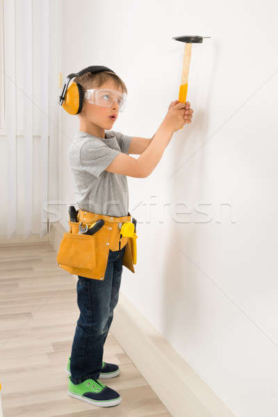 Boy Hammering Nail In Wall Stock photo © AndreyPopov