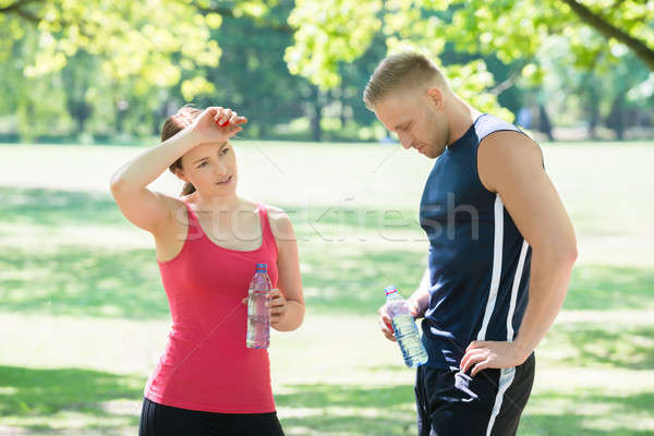 Tired Couple Holding Bottles In Park Stock photo © AndreyPopov