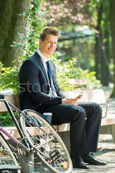 Businessman Sitting On Bench Using Mobile Phone Stock photo © AndreyPopov