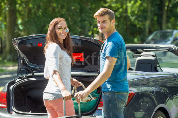 Smiling Couple Putting Luggage In A Car Trunk Stock photo © AndreyPopov
