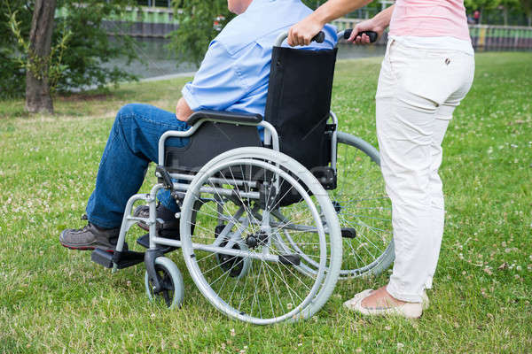 Woman Assisting Disabled Man On Wheelchair Stock photo © AndreyPopov