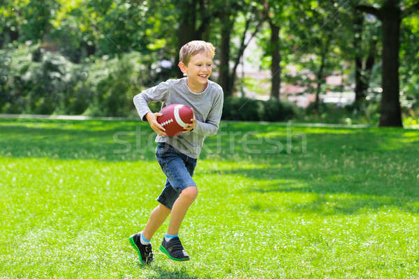 Boy Running With Rugby Ball Stock photo © AndreyPopov