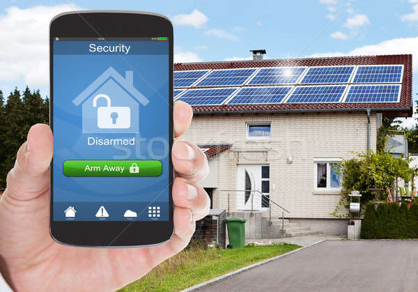 Person Holding Mobile Phone With Home Security System Stock photo © AndreyPopov