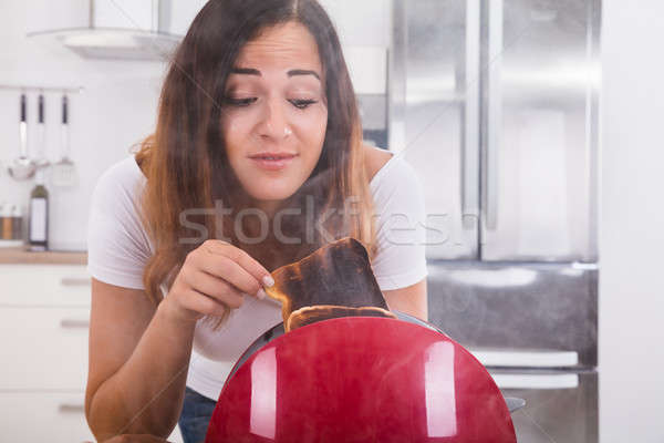 Woman Taking Burnt Toast Out Of The Toaster Stock photo © AndreyPopov