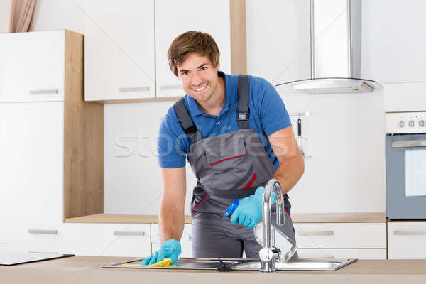 Happy Janitor Cleaning Kitchen Sink Stock photo © AndreyPopov