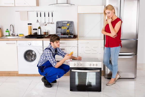 Male Worker Repairing Oven Using Multimeter In Kitchen Stock photo © AndreyPopov