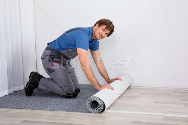 Handyman Rolling Carpet On Floor Stock photo © AndreyPopov
