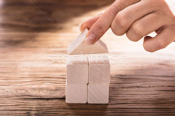 Hand Holding A Roof Of Wooden Block House Stock photo © AndreyPopov