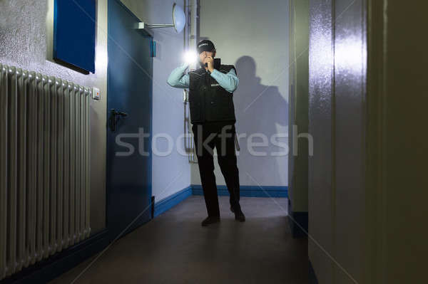 Security Guard With Flashlight Standing In Corridor Stock photo © AndreyPopov