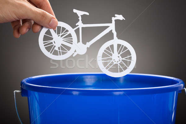 Businessman's Hand Throwing Paper Bicycle In Blue Bucket Stock photo © AndreyPopov