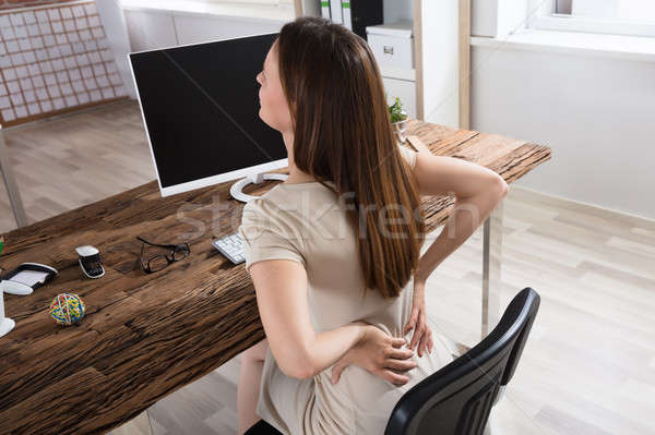 Businesswoman Having Back Pain At Workplace Stock photo © AndreyPopov