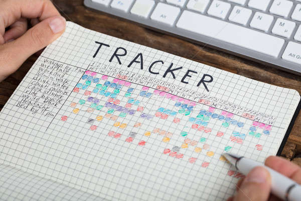 Person Drawing Tracker Chart On Notebook Stock photo © AndreyPopov