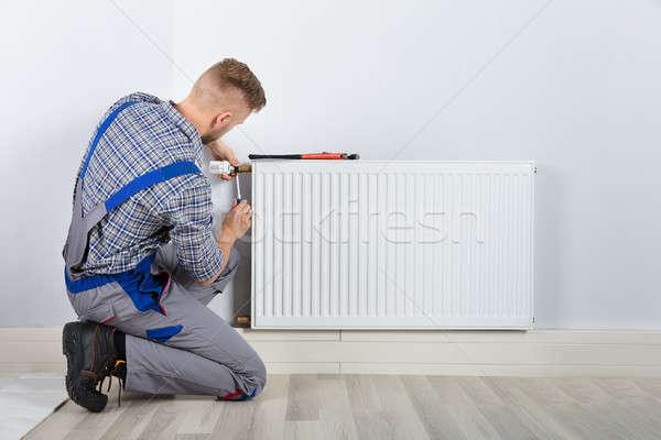 Homme plombier thermostat vue arrière tournevis Photo stock © AndreyPopov