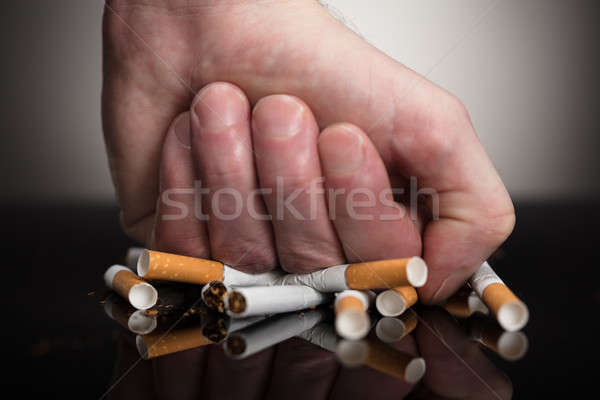 Man's Fist Crushing Cigarettes Stock photo © AndreyPopov