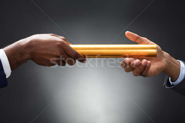 Man Passing The Golden Baton To His Partner Stock photo © AndreyPopov