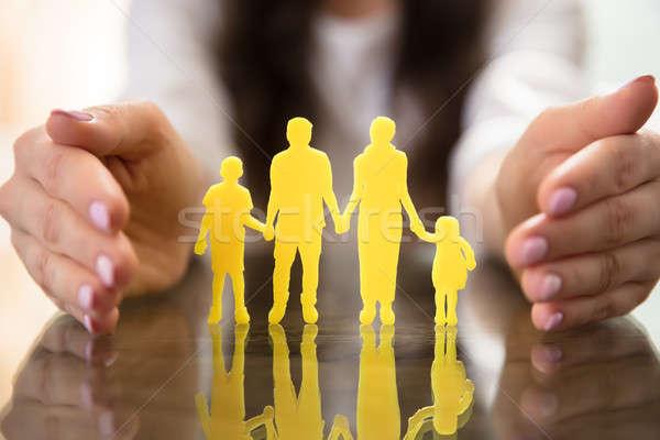 Businesswoman Protecting Family Figures Stock photo © AndreyPopov
