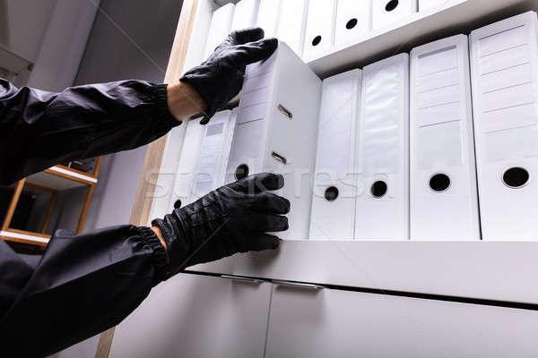 Thief Stealing Folder From Shelf Stock photo © AndreyPopov
