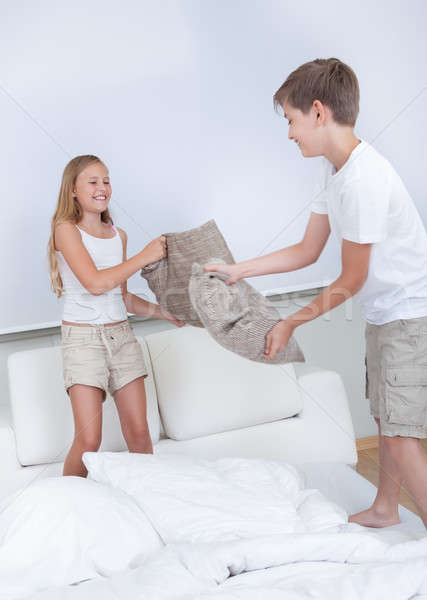 Siblings Having A Pillow Fight Together On Bed Stock photo © AndreyPopov