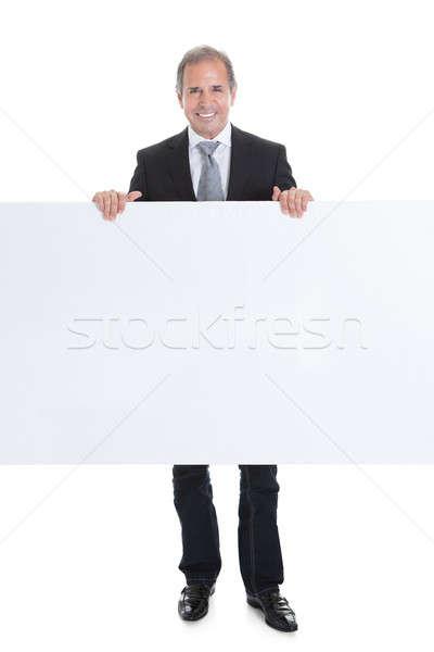 Boldog üzletember tart plakát portré fehér Stock fotó © AndreyPopov