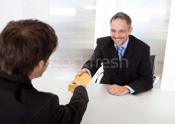 Businessman receiving gold bar Stock photo © AndreyPopov