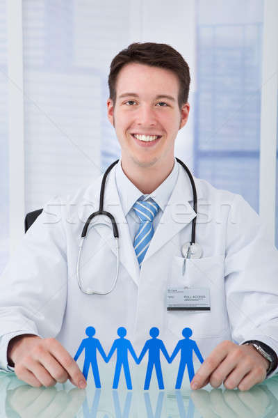 Confident Male Doctor Holding Paper People Chain At Desk Stock photo © AndreyPopov