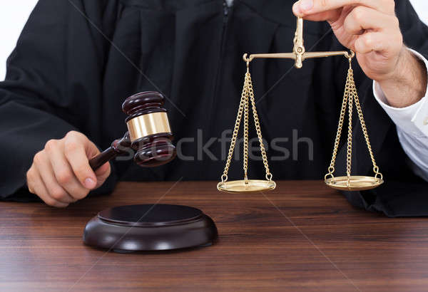 Judge Holding Weight Scale While Striking Gavel At Desk Stock photo © AndreyPopov