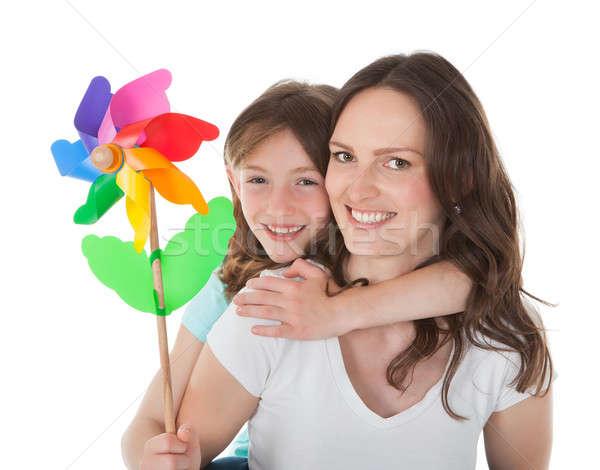 Happy Mother Piggybacking Daughter Holding Pinwheel Stock photo © AndreyPopov