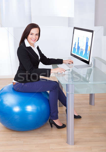 Businesswoman Using Computer While Sitting On Pilates Ball Stock photo © AndreyPopov