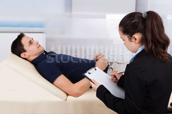 Psychologist Writing Notes While Patient Lying On Bed Stock photo © AndreyPopov