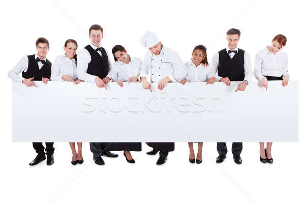 Group of catering staff holding a blank banner Stock photo © AndreyPopov