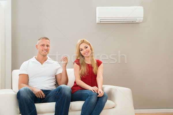 Couple On Sofa Using Air Conditioner Stock photo © AndreyPopov