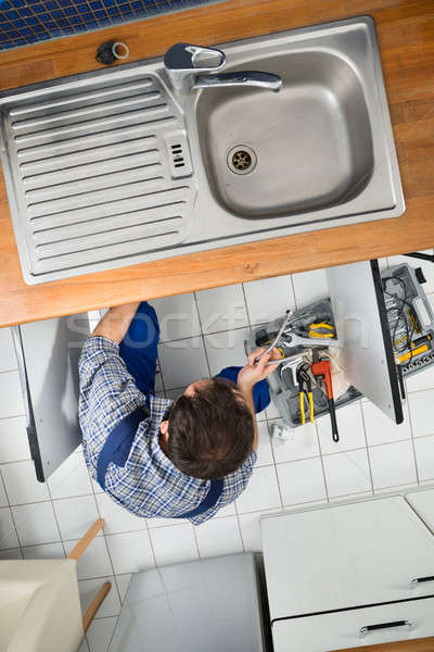 Plumber Repairing Sink In Kitchen Stock photo © AndreyPopov
