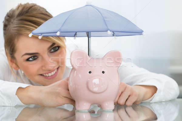 Businesswoman Sheltering Piggybank With Umbrella Stock photo © AndreyPopov