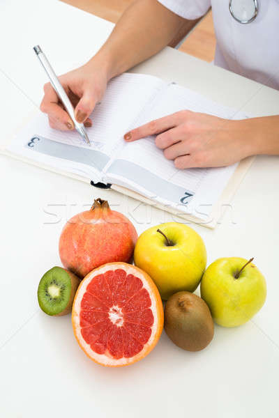 Dietician Writing Prescription With Fruits On Desk Stock photo © AndreyPopov