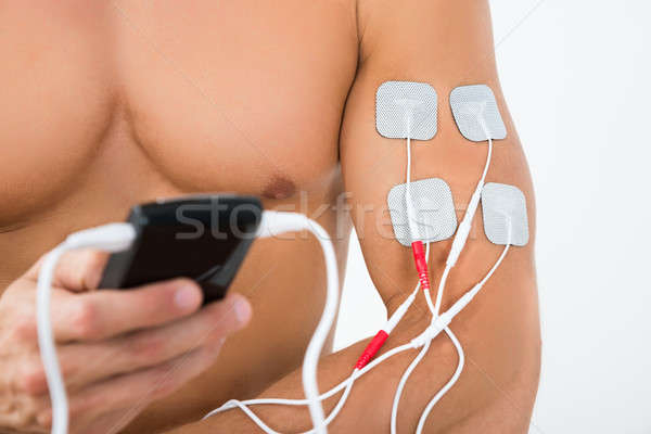 Male Hand With Electrostimulator Electrodes Stock photo © AndreyPopov