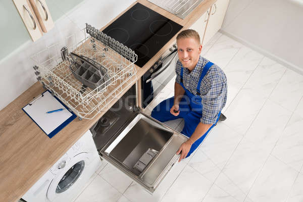Worker With Toolbox Repairing Dishwasher Stock photo © AndreyPopov