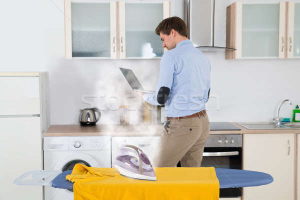 Electric Iron On Cloth While Man With Laptop Stock photo © AndreyPopov