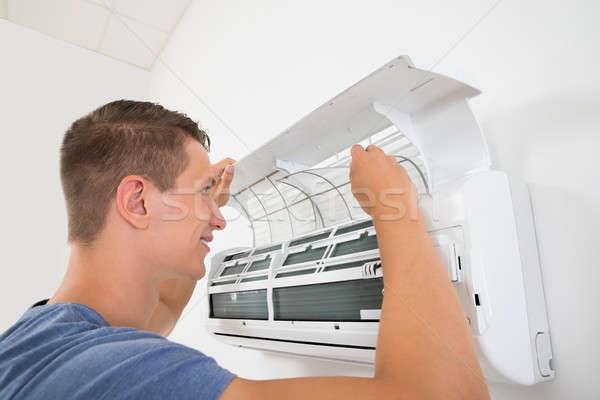 Homem limpeza ar condicionado jovem feliz casa Foto stock © AndreyPopov